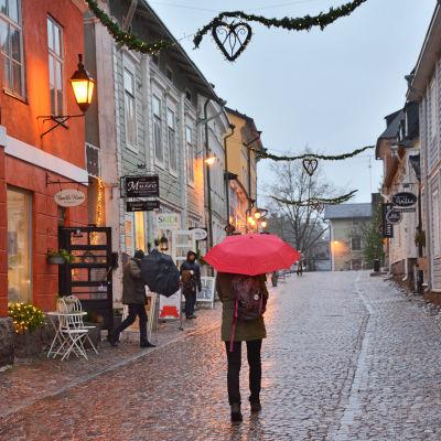En person med rött paraply går på ågatan i Borgå.