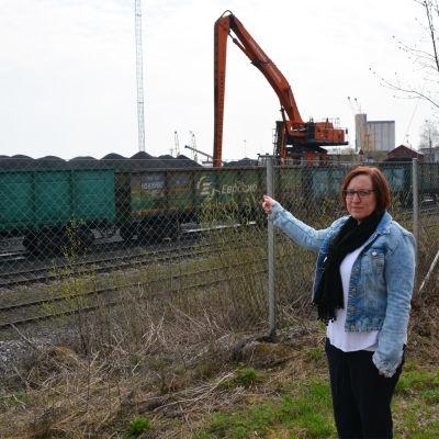 En kvinna står vid ett staket och pekar. Bakom staketet synns tågvagnar, stora kolhögar och en arbetsmaskin.