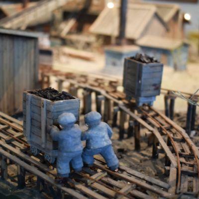 Två små trägubbar skuffar en vagn med kol i en miniatyrmodell av Dalsbruks masugnsområde.