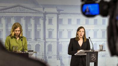 Hanna Kosonen och Li Andersson på en av statsrådets konferenser under pandemiåret 2020. De står vid varsin talstol och Li Andersson har ordet.