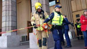 Brandman och polis stänger och vaktar ingångarna till Helsingfors centralstation.