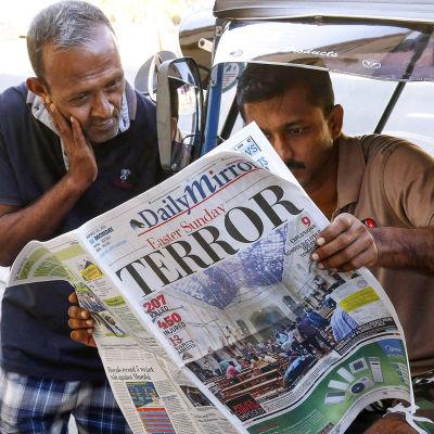 Två personer läser en dagstidning.