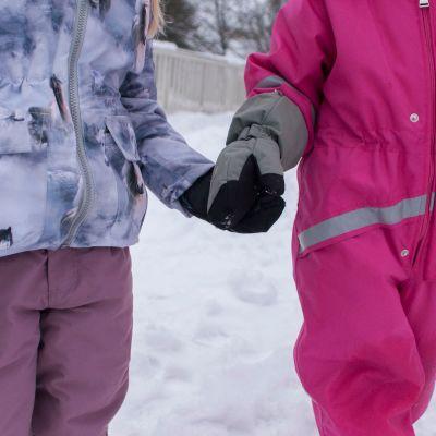 Päiväkotilapset pitävät toisiaan kädestä kiinni.