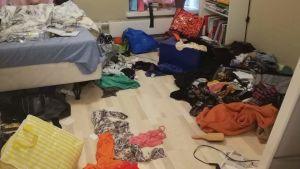 Ostädat sovrum med klädhögar på golvet
