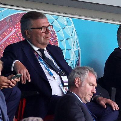 Ari Lahti sitter iklädd kostym på en läktare omgiven av andra åskådare.