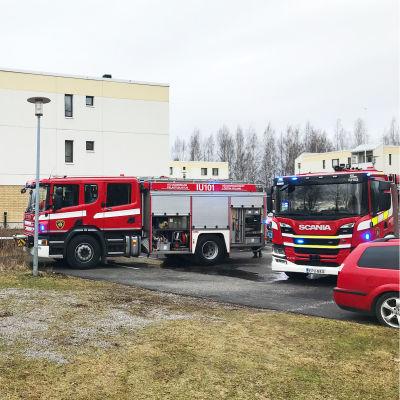 Flera brandbilar står utanför ett höghus.