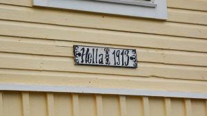 En skylt på en gul trähusvägg. På skylten står det Hella.