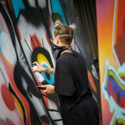 Graffititaiteilija EKA tekee selin kameraan graffititaideteosta värikkäiden seinien keskellä.