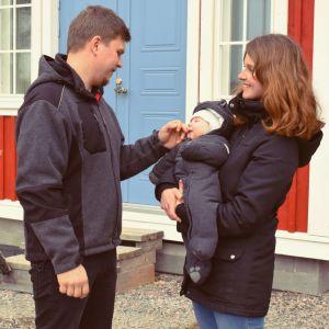 Mathias och Henrika Gustafsson med sin baby framför ett rött hus med blå dörr och vita knutar.