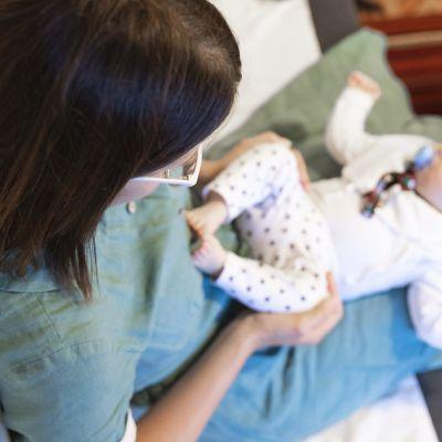 Vauva nukkuu äitinsä sylissä