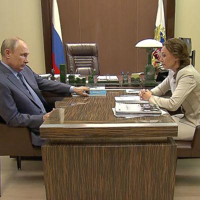 Rysslands president Vladimir Putin och barnombudsman Anna Kuznetsova sitter mittemot varandra vid ett skrivbord och ser allvarliga ut.