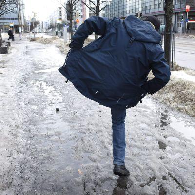 mies liukkaalla kadulla