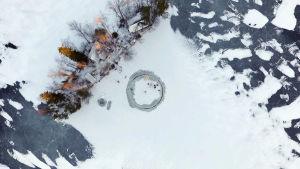 En bild över en sjö där en rund cirkel har sågats ut ur isen.