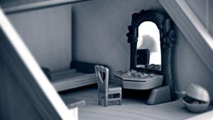 Ett tomt rum i ett dockskåp med en säng utan lakan och ett spegelbord.