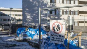 En skylt i förgrunden av en byggarbetsplats varnar folk från att beträda området.