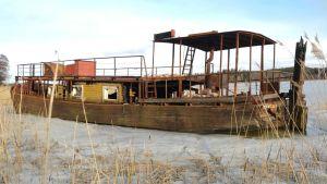 En pråm av trä ligger fastfrusen i en vik. Båten har tak och reling av rostigt järn.