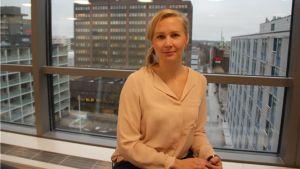 En kvinna, Monna Airiainen, sitter vid ett fönster och tittar in i kameran.