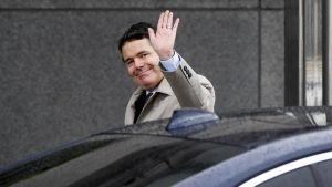 En man i beige jacka stiger ut ur en bil och vinkar.