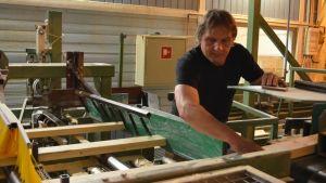 Man vid produktionslinje i träförädlingsfabrik.