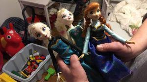 Tre dockor i ett rum med leksaker.