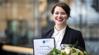 Laura Arikka ler mot kameran med ett diplom och blommor i händerna.