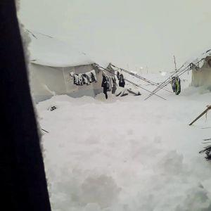 Snö i al-Hol i Syrien. På bilden syns två vita tält och kläder som hänger utanför tälten och som ät täckta med snö.