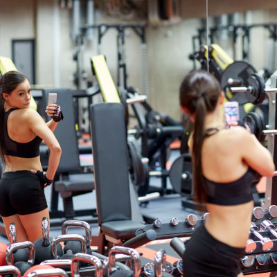 Kvinna tar selfie i en spegel i ett gym.