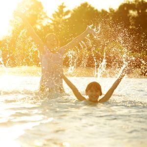 Barn som badar i kvällssol.