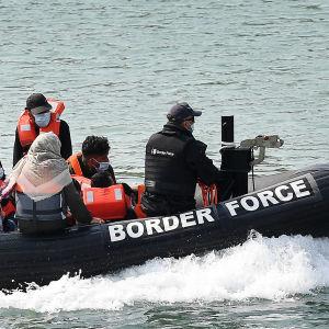 Rajavartiosto kuljettaa pelastusveneellä siirtolaisia Englannin kanaalissa.