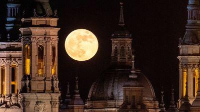 En citrongul enorm måne syns ovanför tinnar och torn mot en svart himmel.