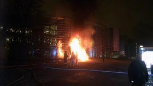 Den brinnande skulpturen med med brandmän i förgrunden.