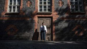 Pia Rickman står framför ett brunt och svart tegelhus.