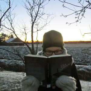 Orfeuksen kääntöpiiri -blogin kirjoittaja Suvi Lindqvist lukee kirjaa talvisessa maisemassa.