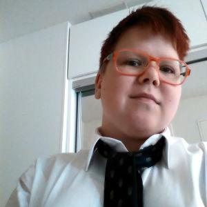 Eri Lassila, iklädd skjorta och slips. Har också på sig orange glasögon.