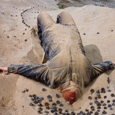 Haalaripukuinen henkilö makaa hiekassa käpyjen keskellä punainen huivi kasvojen suojana Turppi-ryhmän maataideteoksessa Muurahaiskuningatar Lehtimäessä 1982.