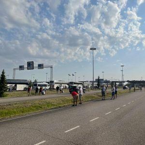 Kuva raja-asemalta, bussijono ja ihmisiä. Aurinko paistaa.