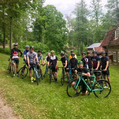 Ett tjugotal cyklister som står vid sina cyklister på rad.
