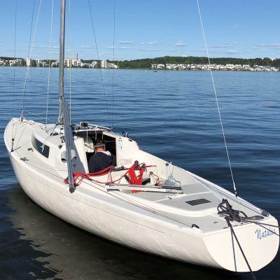 H-segelbåt i vattnet. Vädret är klart och små vågor rör sig på havsytan.
