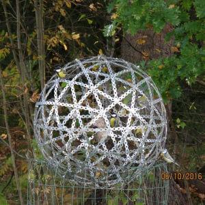 Fågelmatare omgiven av ett stort bollformat skyddsnät av stålband.