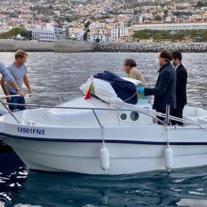 Tre män i en motobot räcker över varor till två män i en segelbåt. Männen i motorbåten har på sig munskydd och plasthandskar.