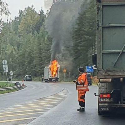 En väg med utryckningsfordon och ett större fordon av modell lastbil står vi kanten av vägen och det slår ut eld ur den.