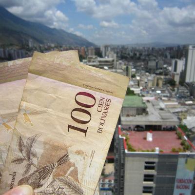 Bolivar-sedlar med värdet 100 från Venezuela. I bakgrunden bild på stad med skyskrapor.
