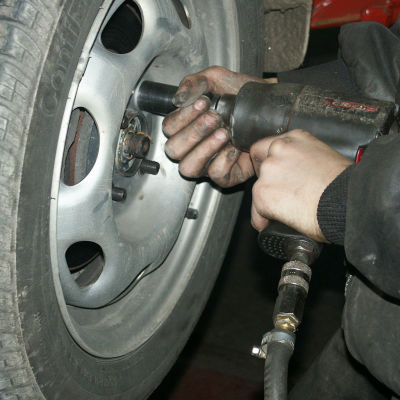 Ett par oljiga händer håller i en bultdragare och tar bort bultarna från ett sommardäck.