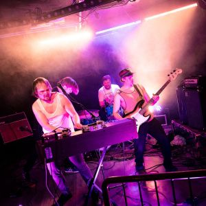 Neljän miehen bändi soittaa lavalla hikisinä ja energisinä. Lavalla on savua ja violettia valoa.