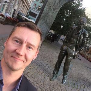 En leende Veli-Pekka Tynkkynen i Moskva vid idolen, sångaren Bulat.