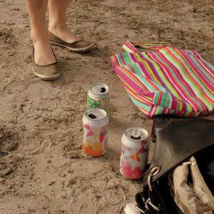 Siderburkar, en randig tygväska och en ungdom som står på stranden.