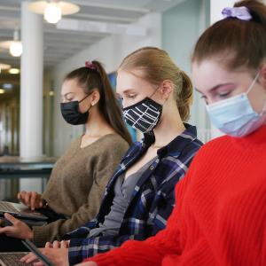 Studerande som har munskydd på sig och som sitter framför sina bärbara datorer vid en soffa i Svenska social- och kommunalhögskolans utrymmen i Kronohagen i Helsingfors.