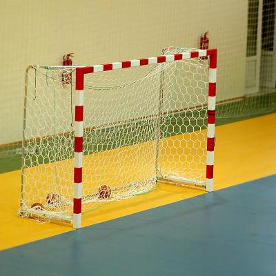 Ett tomt handbollsmål på an handbollsplan inomhus.