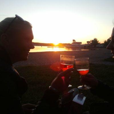 Två kvinnor dricker vin på stranden