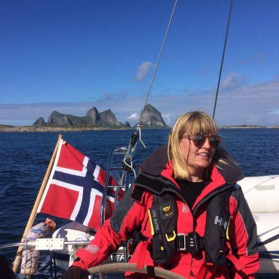 Linda Karlsson på en segelbåt med norska flaggan och höga berg i bakgrunden.